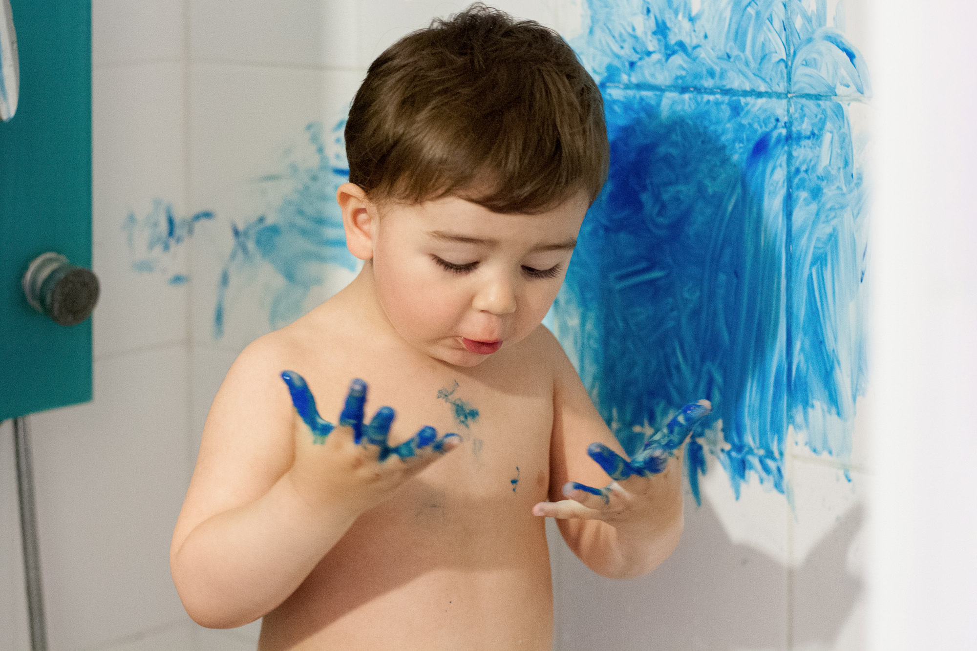 Little boy makes a mess with blue paint. Make sure you're covered in case your toddler gets up to mischief with personal liability included with your travel insurance cover.